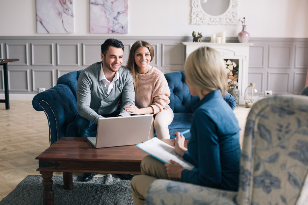 Successful agent giving consultation to family couple about buying house.