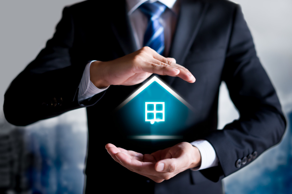 Protecting gesture of man and symbol of house. Property insurance protection concept.
