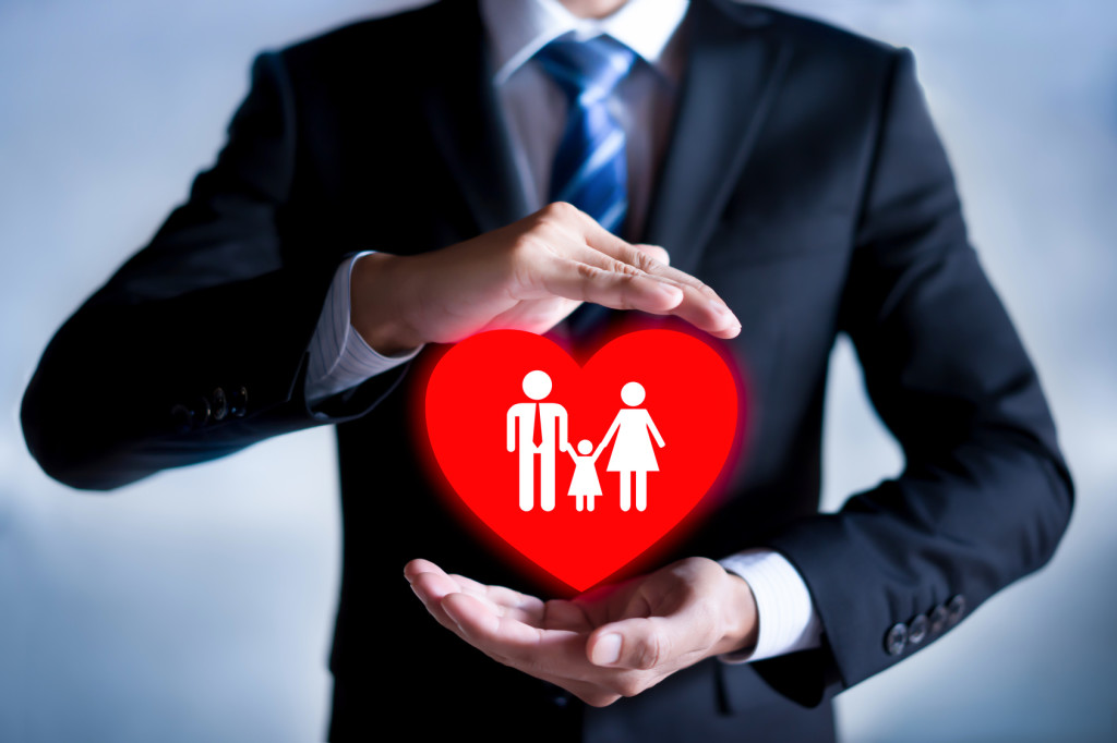 Family life insurance, family services and supporting families concepts. Businessman with protective gesture.